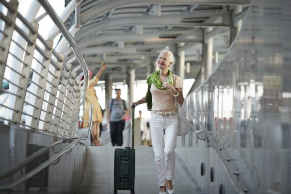 Senior woman with luggage at railroad station
