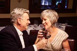 Couple toasting with red wine in restaurant