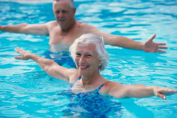 Portrait of a senior couple stretching in a swimming pool