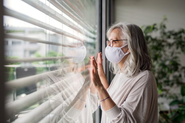 Portrait of senior woman with face mask standing indoors by window at home, looking out.