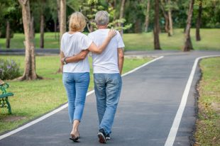 Rear View Of Couple Walking On Footpath In Park
