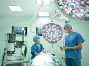 Orthopaedic surgeon and nurse preparing patient for hip surgery in operating theatre